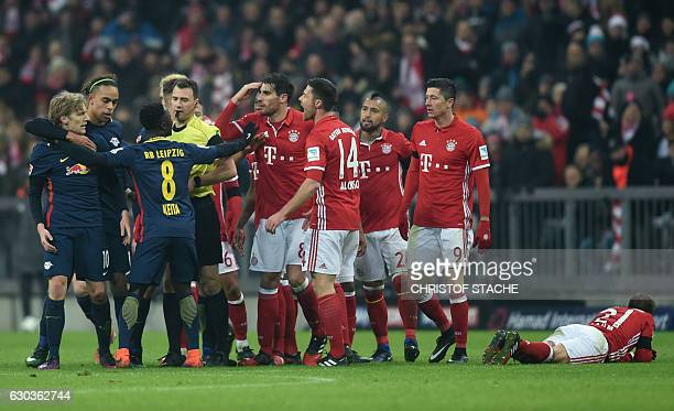Several Bayern Munich players and Leipzig players discuss with the referee Felix Swayer after an attack of Leipzig's Swedish midfielder Emil Forsberg...