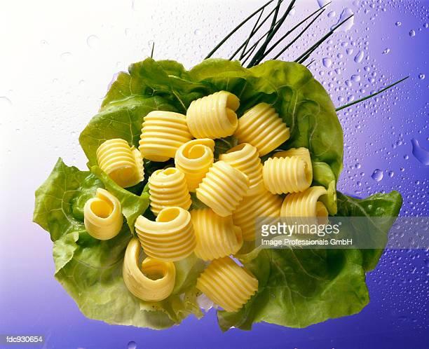 Several butter curls arranged on a lettuce leaf