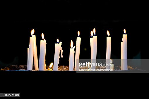 Several candlelights lit up against black background : Stock Photo