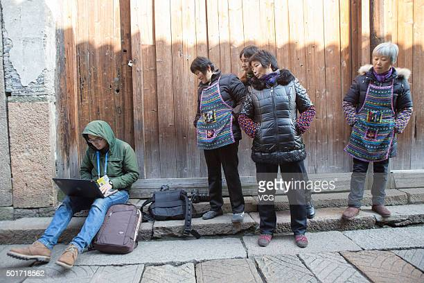 Several citizens crowd to look at a Shanghai reporter acting on press releases about the Second World Internet Conference in Wuzhen ancient town on...