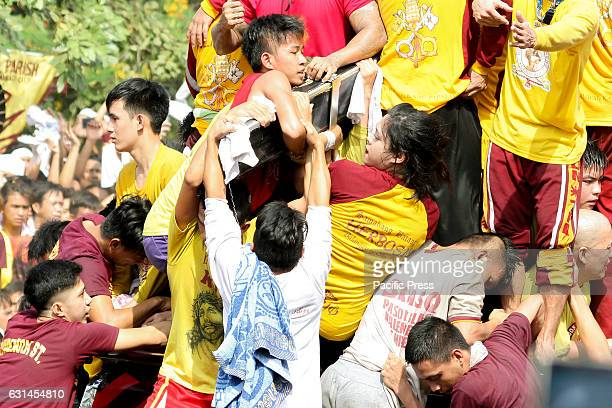 AVE MANILA NCR PHILIPPINES Several devotees including a lady grab on to and kiss the cross of the miraculous Icon of the Black Nazarene Devotees...