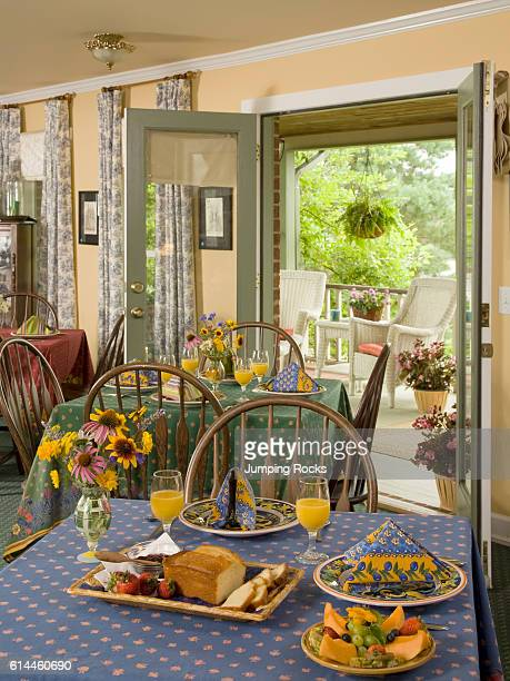 Several dining tables with breakfast place settings and open doors leading to porch Mont Eagle Inn Tennessee USA
