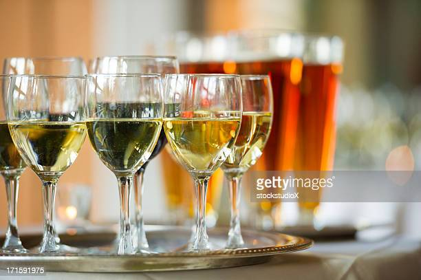 Several glasses of wine and beer on a serving tray