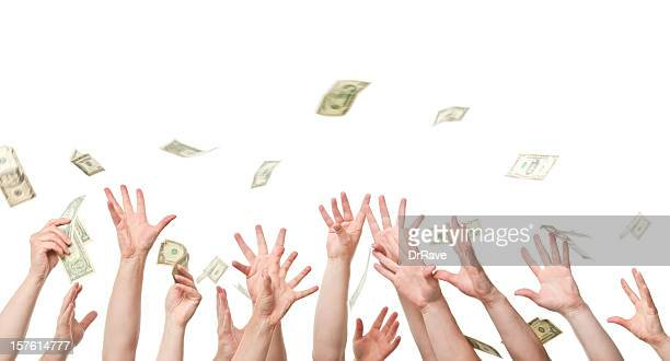 Several hands reaching out to grab dollars raining