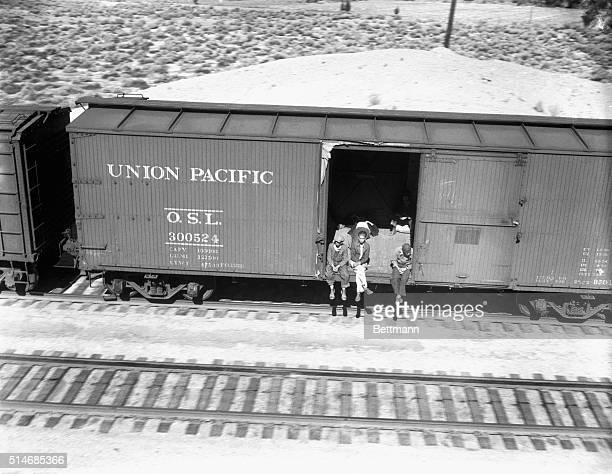 Several hobos ride a freight car hanging over the side while others lay in the shade behind them These hobos ride empty freight carts to Southern...