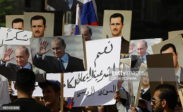 Several hundred people holding up portraits of Syrian President Bashar alAssad and his Russian counterpart Vladimir Putin gather near the Russian...