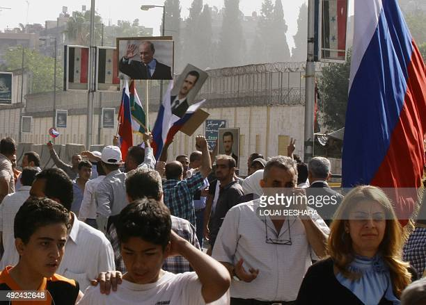 Several hundred people holding up Russian and Syrian flags as well as portraits of the two countries' presidents gather near the Russian embassy in...