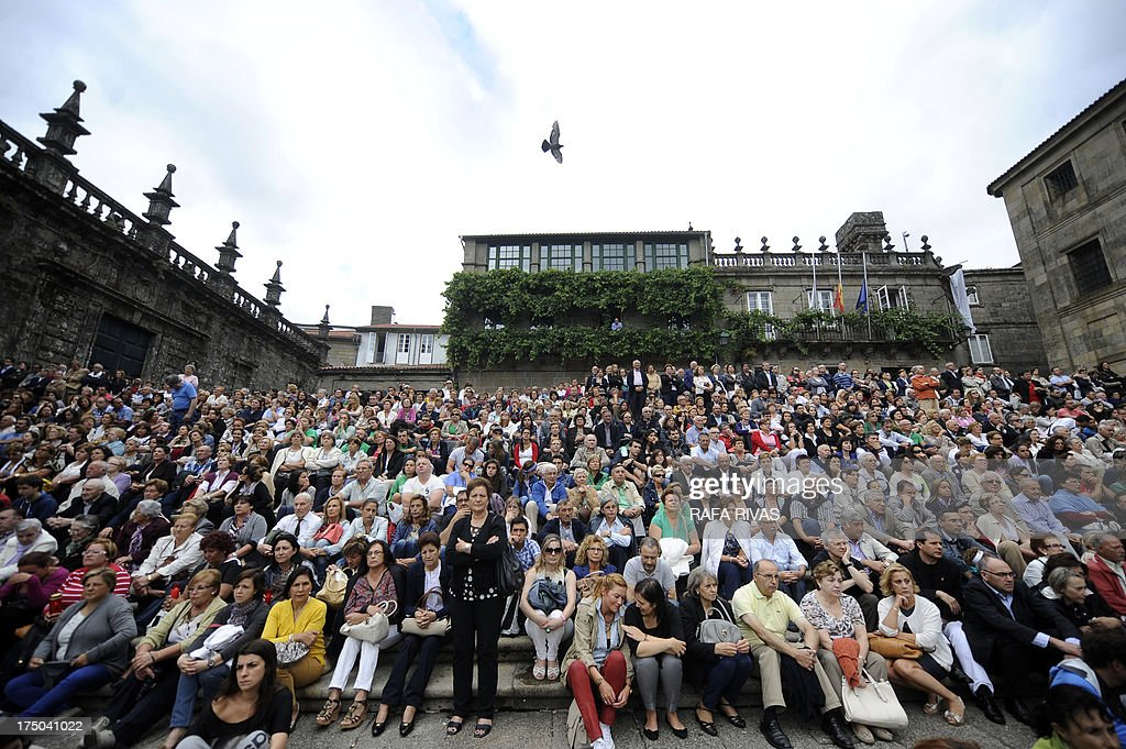 Several hundreds of people watch the memorial ceremony of the victims of the derailed train of Angrois on a giant screen at the Quintana Square, behind the Cathedral of Santiago de Compostela on July 29, 2013. The driver of a train that hurtled off the rails in Spain was charged on July 28 with 79 counts of reckless homicide and released on bail after being questioned by a judge.