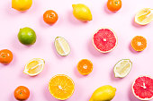 Several kinds of whole and cut citrus on a pink background. Top view