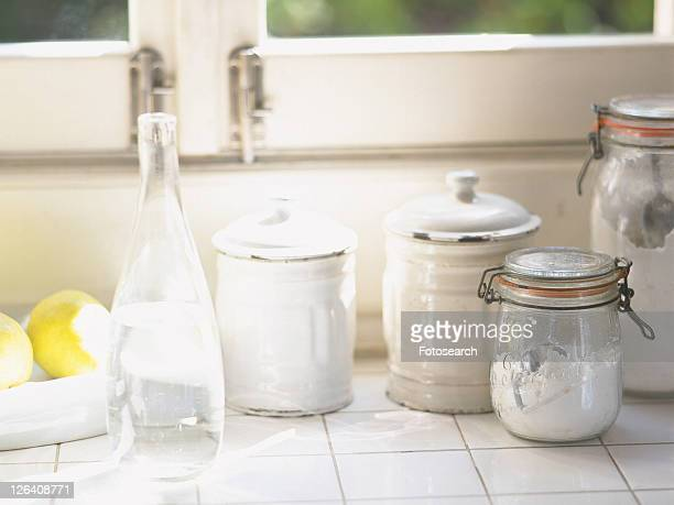 Several Kitchen Items, Such as Bottles and Tins Next to a Window, Front View