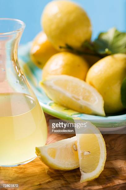 Several lemons with leaves, lemon wedges, lemon juice