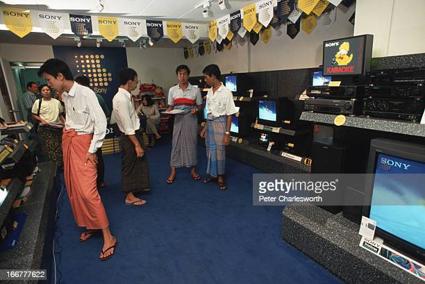BURMA YANGON RANGOON MYANMAR Several male customers wearing traditional Burmese longyis look at all the latest electronic devices on sale in the Sony...