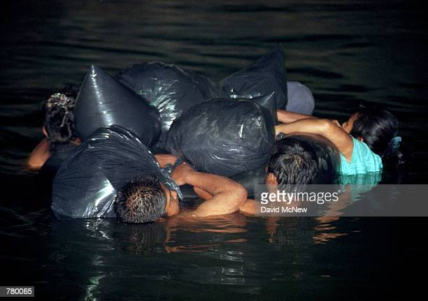 Several men and a woman in a nighttime attempt to elude United States Border Patrol agents cling to garbage bags containing dry clothing as they...
