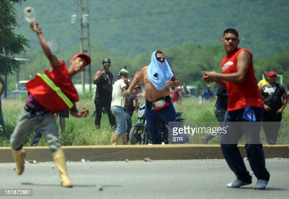 Several men throw objects during before arrival of Venezuelan opposition candidate Henrique Capriles Radonski in Puerto Cabello Venezuela on...