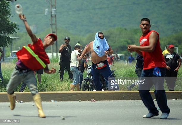 Several men throw objects during before arrival of Venezuelan opposition candidate Henrique Capriles Radonski in Puerto Cabello Venezuela on...