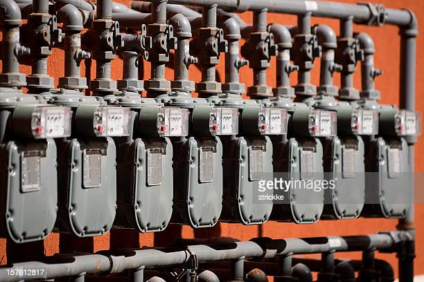 Several Natural Gas Meters in a Row on Orange Wall