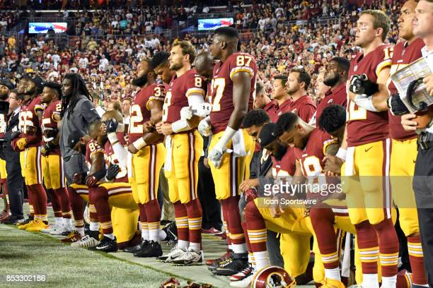 Several of the Washington Redskins kneel during the national anthem during an NFL game between the Oakland Raiders and the Washington Redskins on...