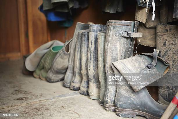 Several pairs of muddy wellington boots on a stone floor.