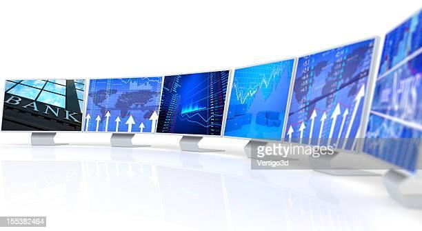 Several PC monitors displaying business charts and data