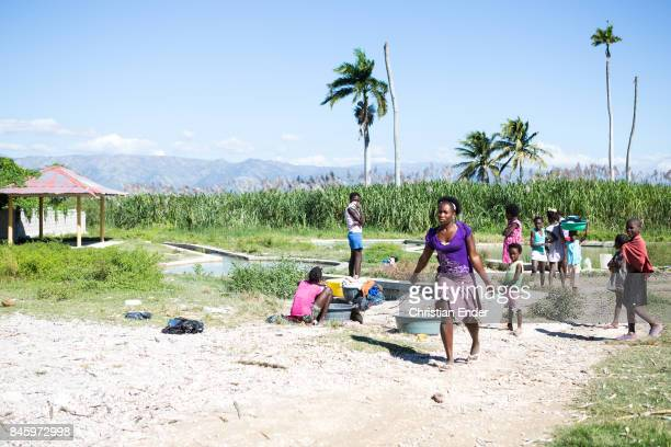 PortauPrince Haiti December 09 2012 Several people doing their laundry at a water basin near PortauPrince Also this area was strongly affected by the...