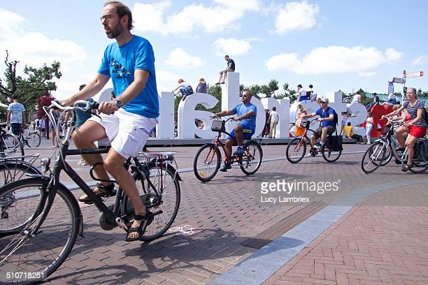 Several people on their bikes with 'I amsterdam' sign in the background Bicycle lane tile incorporated in the bike lane