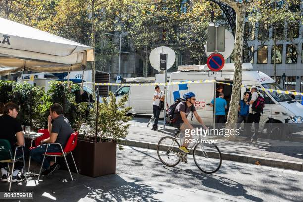 Several people sit on the terraces of a bar next to the mobile units of international broadcasters While the Spanish President Mariano Rajoy told at...