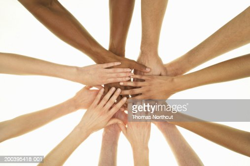 Several people stacking hands on top of each other, overhead view : Stock Photo