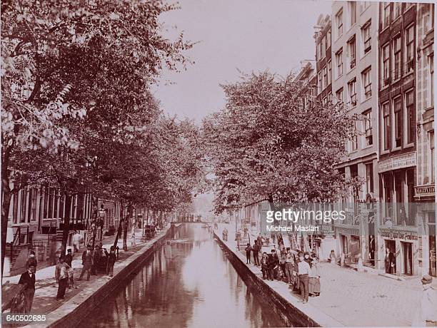 Several people stand along a canal in Amsterdam the Netherlands ca 1880s1890s