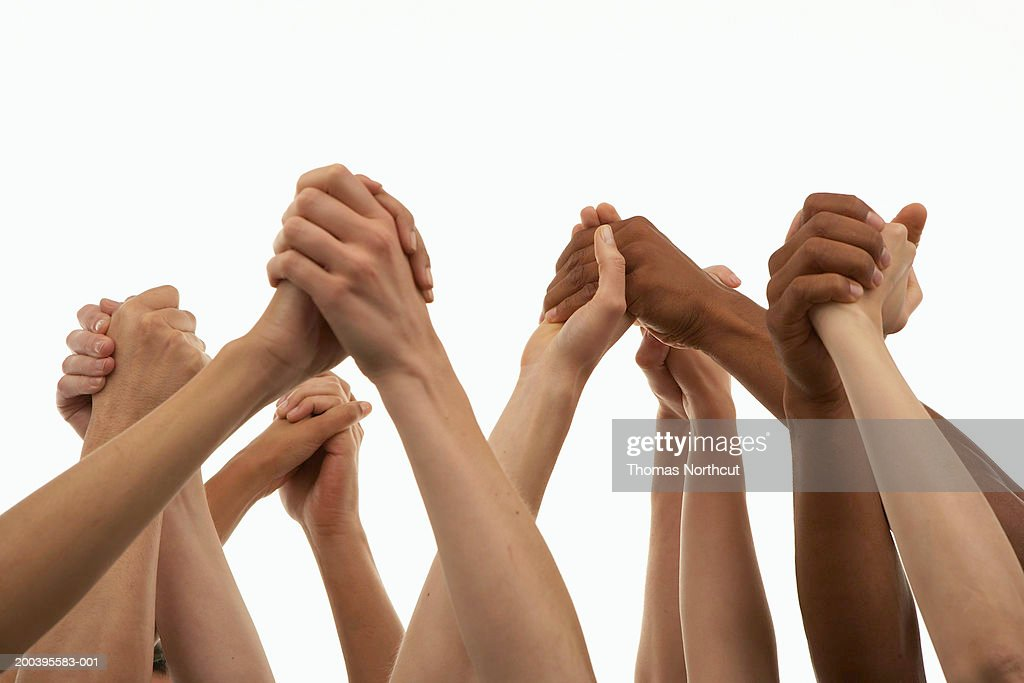 Several people with arms raised, holding hands, low angle view