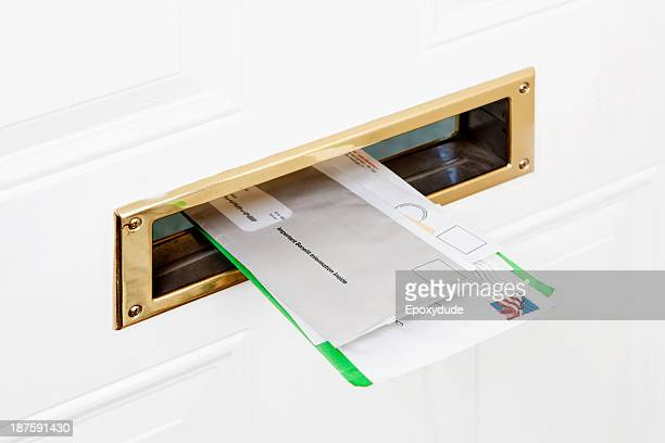 Several pieces of mail stuck in a front door mail slot, close-up