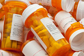Bottles of prescription medicine in a pile. This collection of pill bottles is symbolic of the many medications senior adults and chronically ill people take.