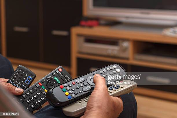 Several remote controls in hands of a man.