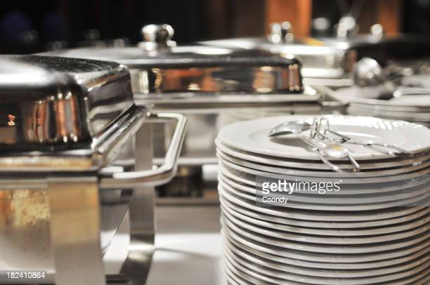 Several stacks of ceramic plates next to metal food trays