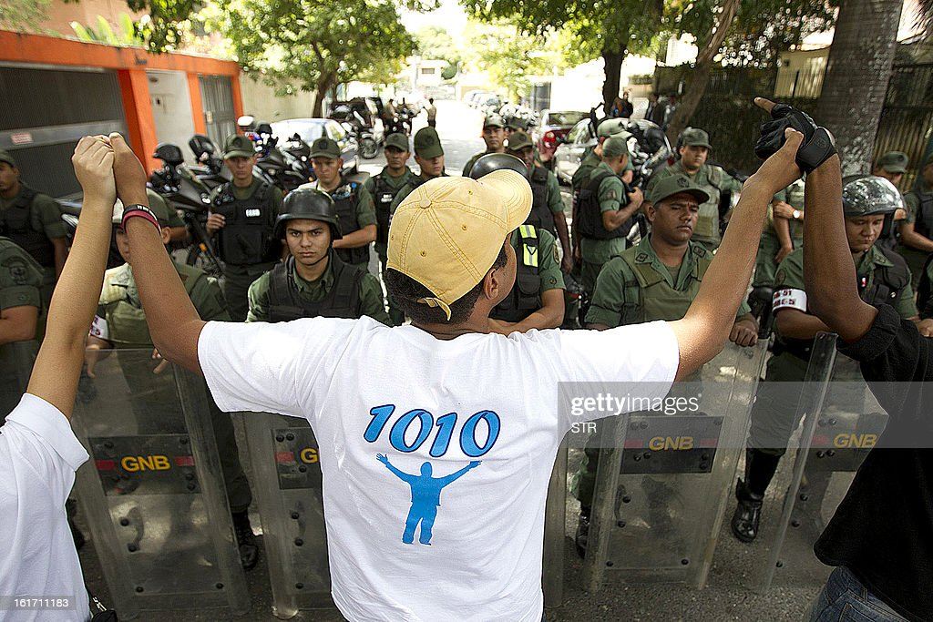Several students demonstrate as members of the National Guard form a barricade in front of the Cuban Embassy in Caracas on February 14, 2013. The demonstrators were demanding the release of seven college students that were arrested hours earlier, while protesting that the 'Castro brothers are ruling Venezuela' while President Hugo Chavez is hospitalized there.