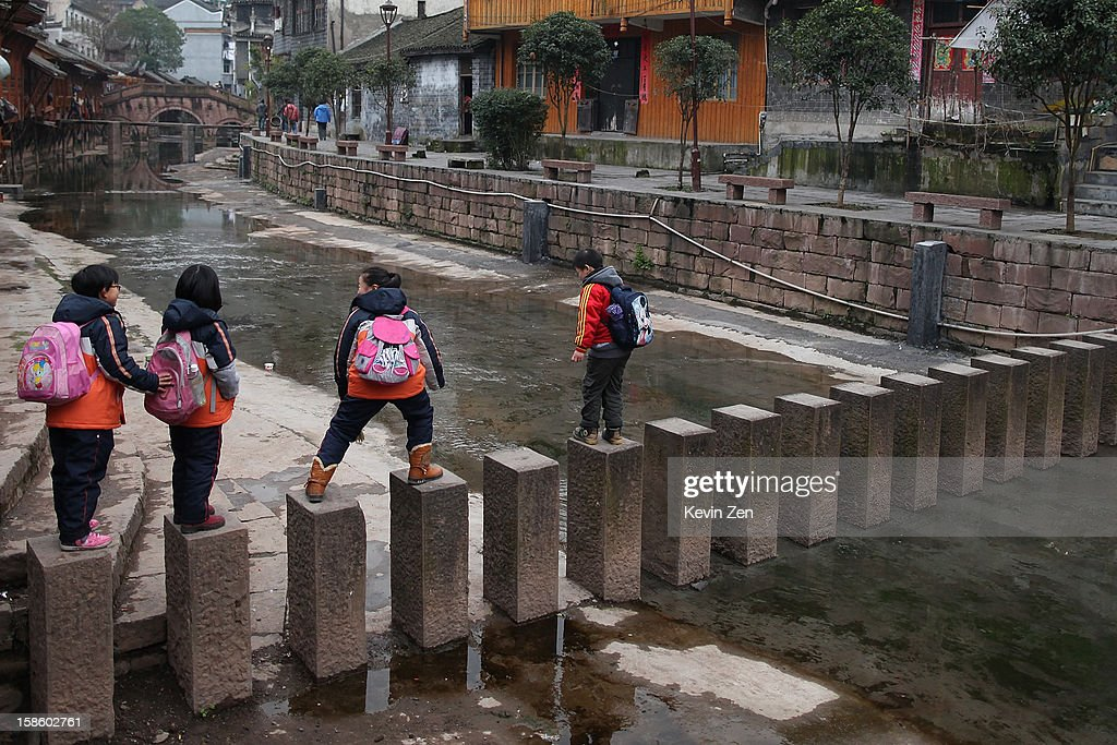Several students go through a stone bridge on December 18, 2012 in Fenghuang, China. Fenghuang Town was built by Emperor Kangxi in 1704 and after 300 years, the city's ancient appearance has been well preserved. Hunan is located in southwest Hunan Provience of China with a population of 370,000 within a total area of 1700 square kilometers.