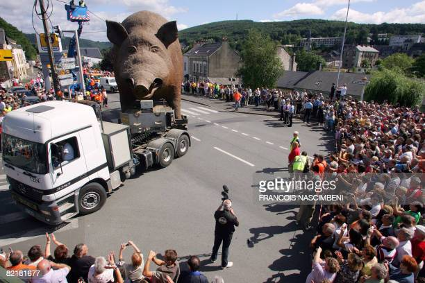Several thousand people watch Woinic a giant wild boar sculpture by Eric Sleziak pulled by a truck on August 5 2008 on a street in BognysurMeuse...