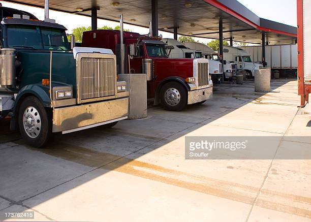 Several trucks at a rest stop gas station filling up tanks