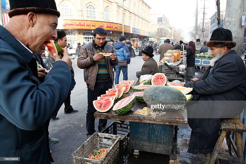 Several Uighur people eat watermelons on the street in Kashgar, on December 10, 2012 in Kashi, China. Kashgar is home to the ethnic Uyghur Muslim community.
