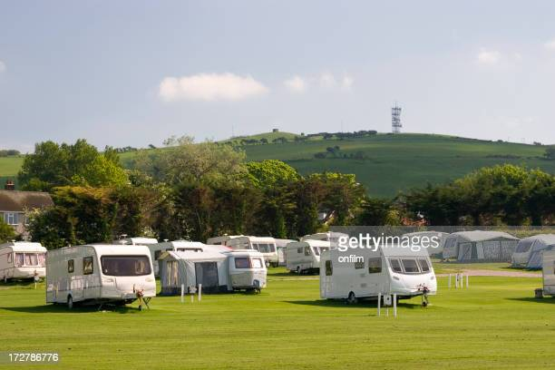 Several white caravans parked on green field