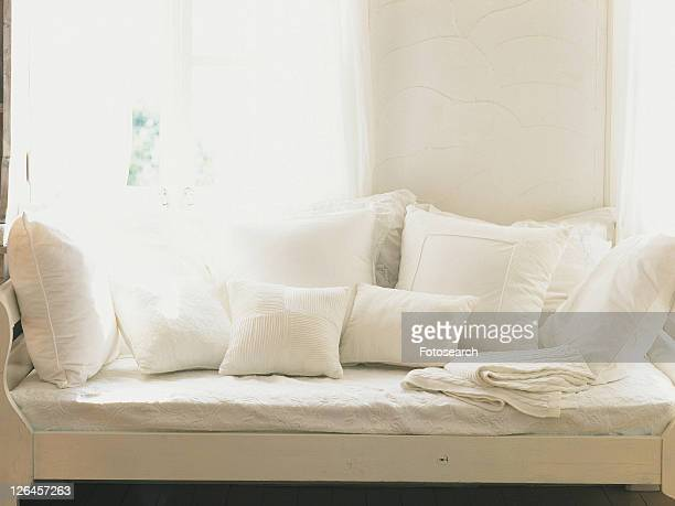 Several White Cushions on a White Sofa Near a Window, Front View