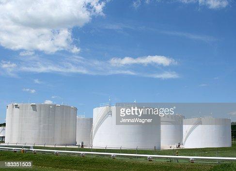 Several white storage tanks in a grassy field