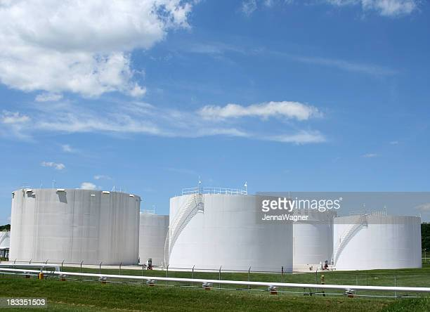 Several white storage tanks in a grassy field