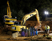 Several woman and rescuers watch as large construction equipment is used to remove flood debris from Short Creek as it crosses Central Street on...