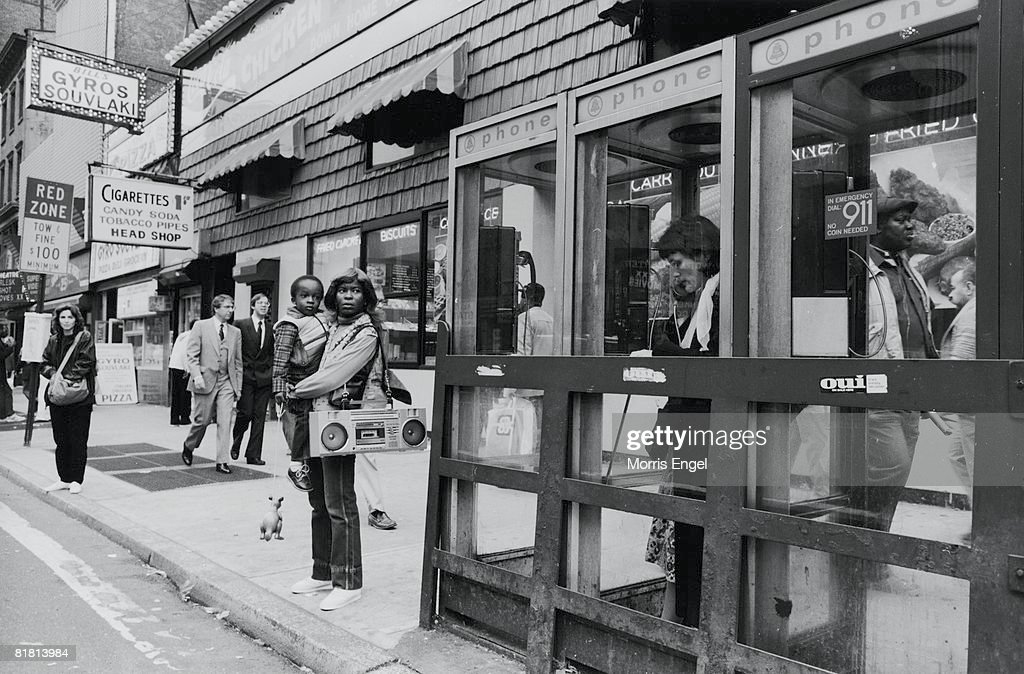 Several women, one with a child her arms and a large radio over her shoulder, waith for a bus while neaby, another woman talks on the phone in a telephone booth, New York, New York, late 1970s or early 1980s.
