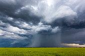 Rotating, threatening cumulonimbus storm clouds with rain-shaft over farmland.  Horizontal, copy space.