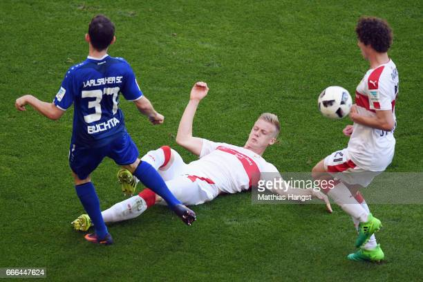 Severin Buchta of Karlsruhe is challenged by Timo Baumgartl and Benjamin Pavard of Stuttgart during the Second Bundesliga match between VfB Stuttgart...