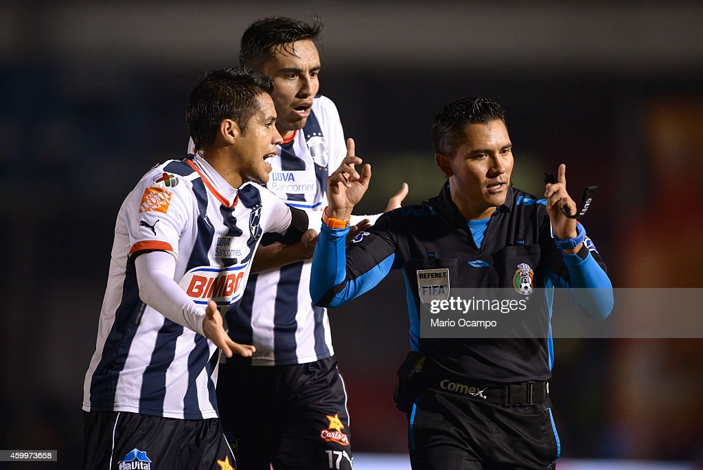 Severo Meza and Jesus Zavala of Monterrey argue with referee Fernando Guerrero during a semifinal first leg match between Monterrey and America as...