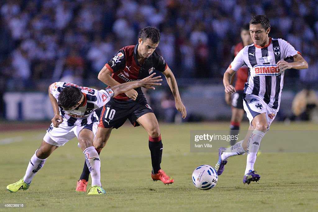 Severo Meza of Monterrey competes for the ball with Maicon Leite and Nery Cardozo of Atlas during a match between Monterrey and Atlas as part of 10th...