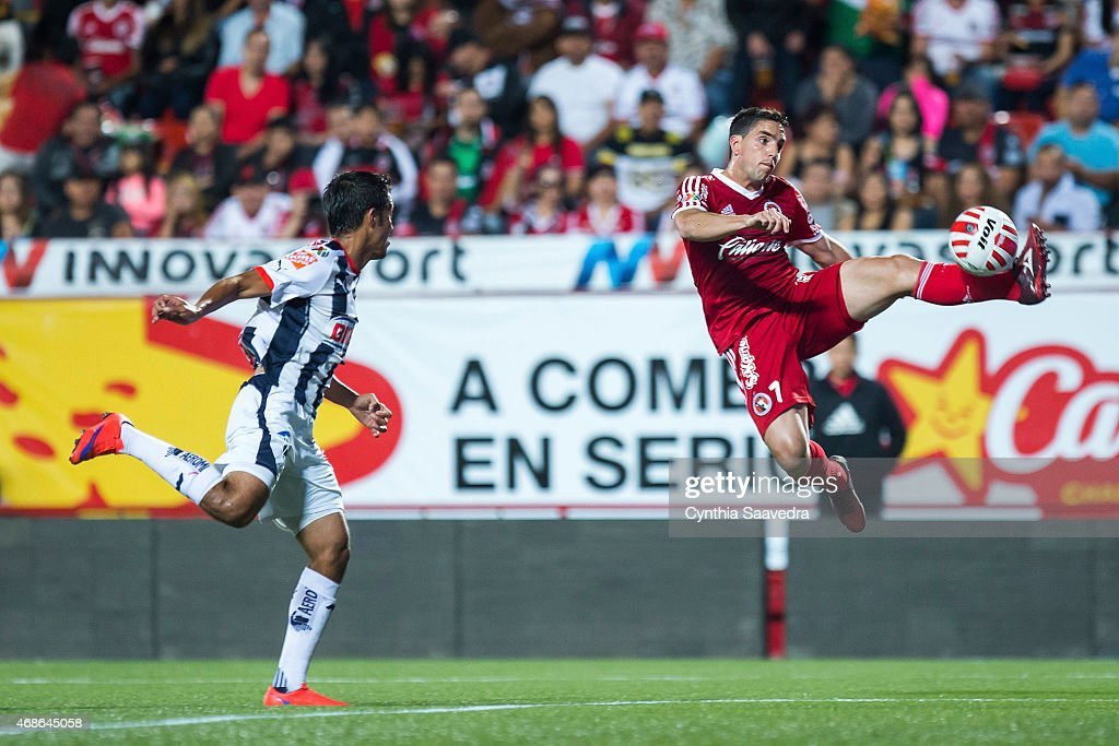 Severo Meza of Monterrey fails in rejecting the ball as Gabriel Hauche of Tijuana tries to control it during a match between Tijuana and Monterrey as...
