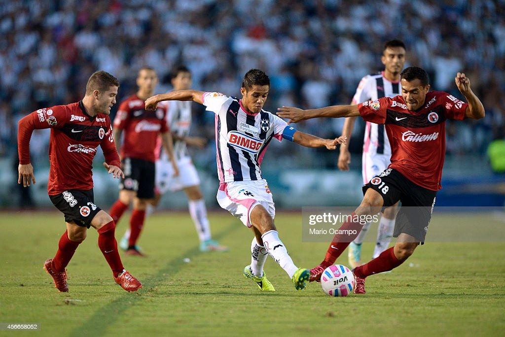 Severo Meza of Monterrey fights for the ball with Greg Garza and Juan Arango of Tijuana during a match between Monterrey and Tijuana as part of 12th...